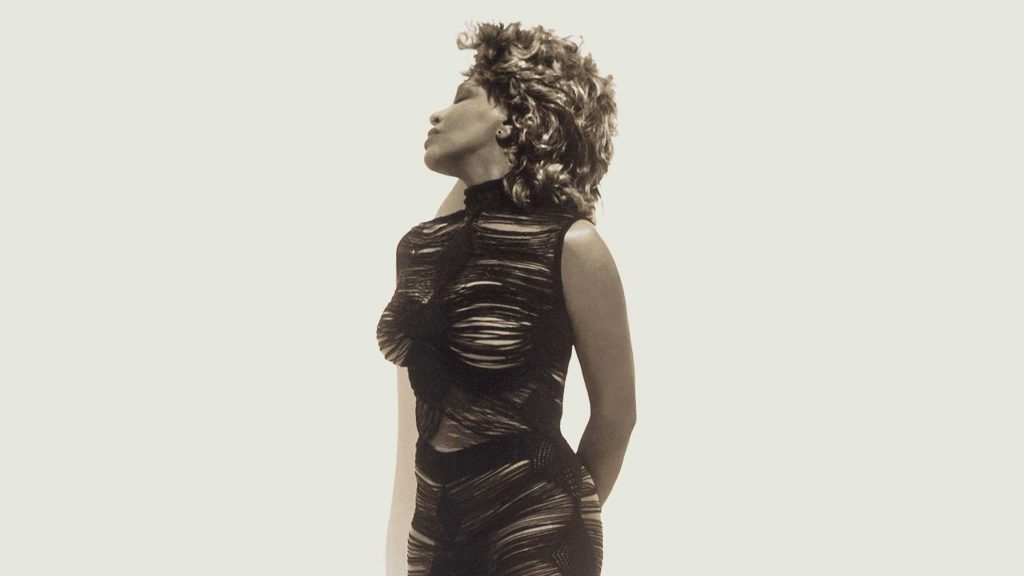 Tina Turner in a fitted black dress with her head turned to the side.