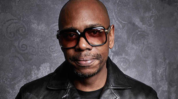 A close-up of Dave Chapelle in large, squarish black glasses and a black leather jacket.