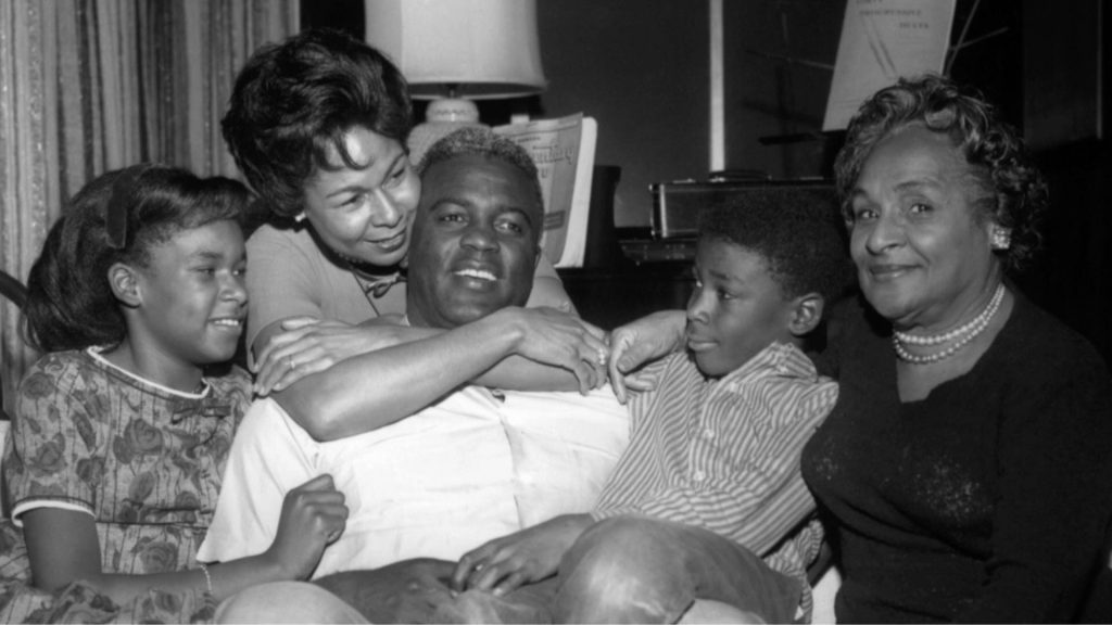 A black-and-white photo of Jackie Robinson with a young boy on his lap, a young girl at his side, being hugged by a young woman, with an older woman seated next to Jackie and the boy.
