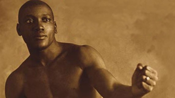 An old photo of Jack Johnson bare-chested in a boxing pose.