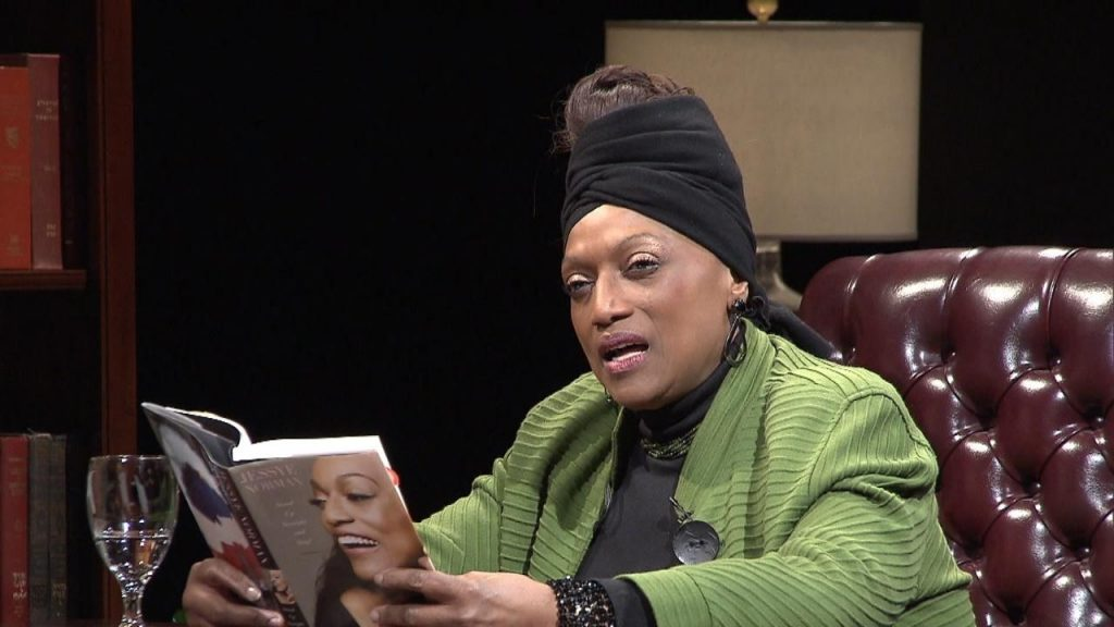 Jessye Norman seated on set in a green jacket holds a copy of her memoir.
