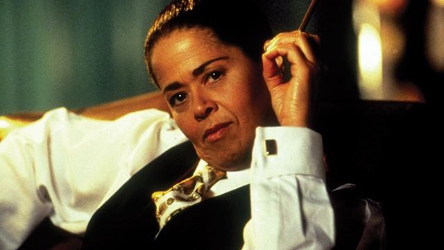 Anna Deavere Smith seated in a white shirt with cuff links and black vest.