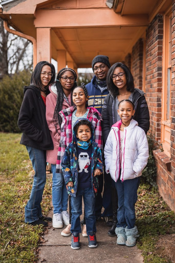 Kendra Thacker-Dickinson posed as a group with her husband and five children on a sidewalk in front of their house.