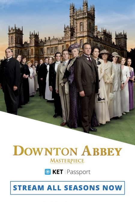 The season 1 cast of Downton Abbey lined up in a zigzag line in front of the castle.
