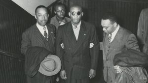 Front, left to right: Leroy Carter, Isaac Woodard, and Donald Jones, NAACP assistant field secretary. Willie Mabry, Sgt. Woodard's cousin. in background. Likely taken while Woodard was on his speaking tour with the NAACP. 10/1946.