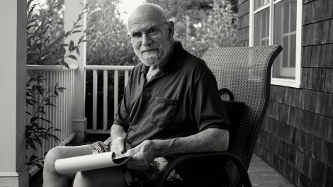 Black and white photo of Oliver Sacks in 2015, sitting on his porch with a pad of paper