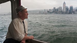 Mark Rylance on a ferry boat looking over the water toward the Hong Kong skyline on a gray, overcast day.