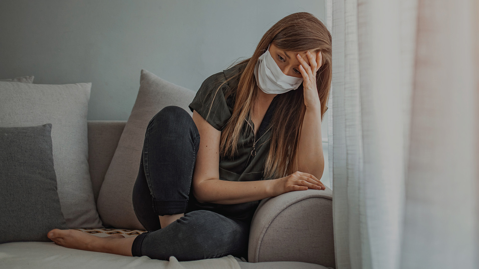 Young woman on a couch wiht a mask