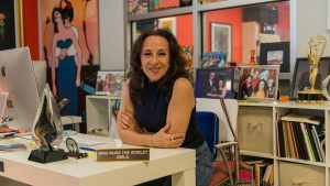 Journalist Maria Hinojosa at a desk in her office, smiling at the camera
