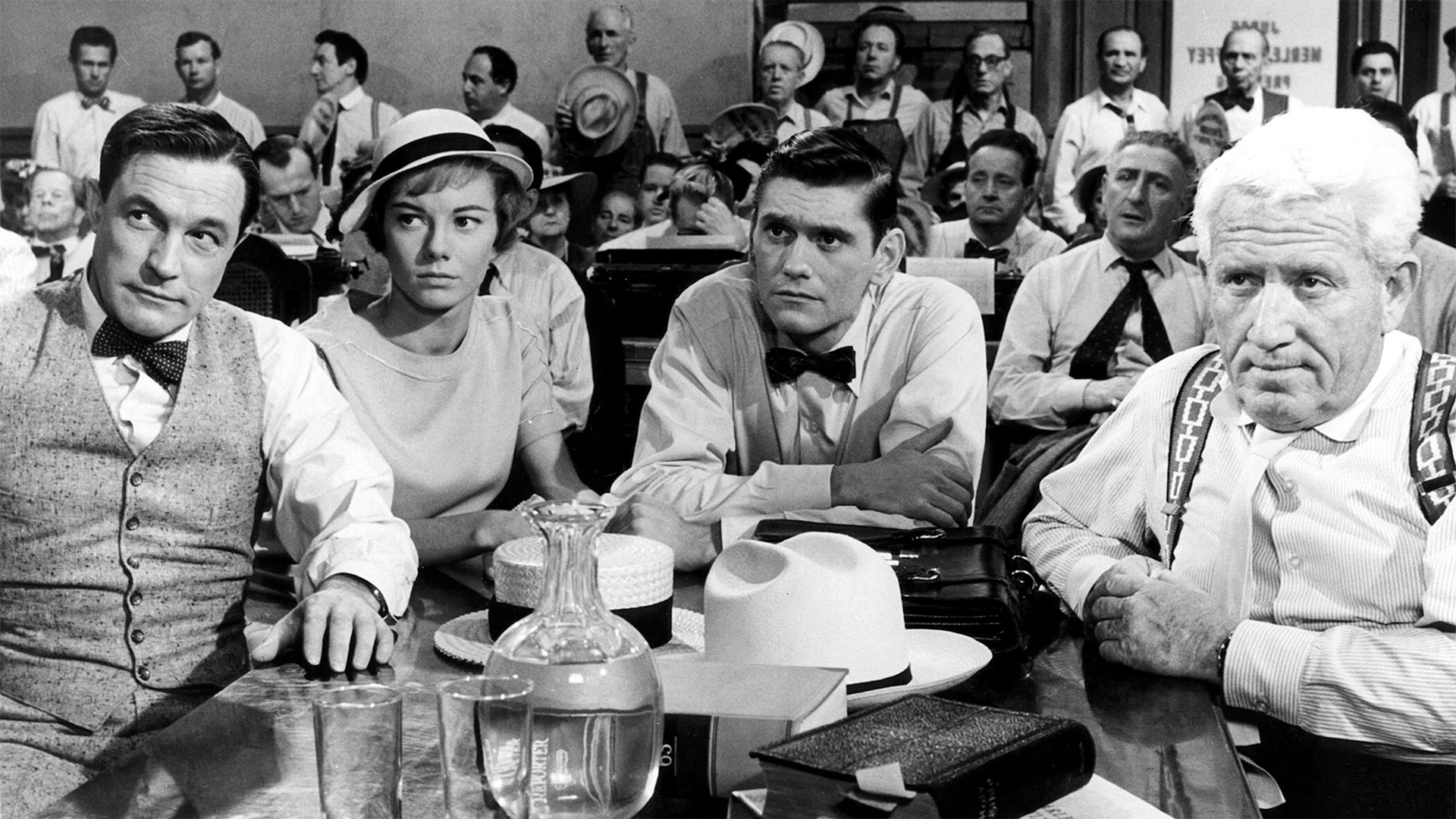 Black and white screen still of three men and a woman sitting at a table at the front of what appears to be a courtroom.