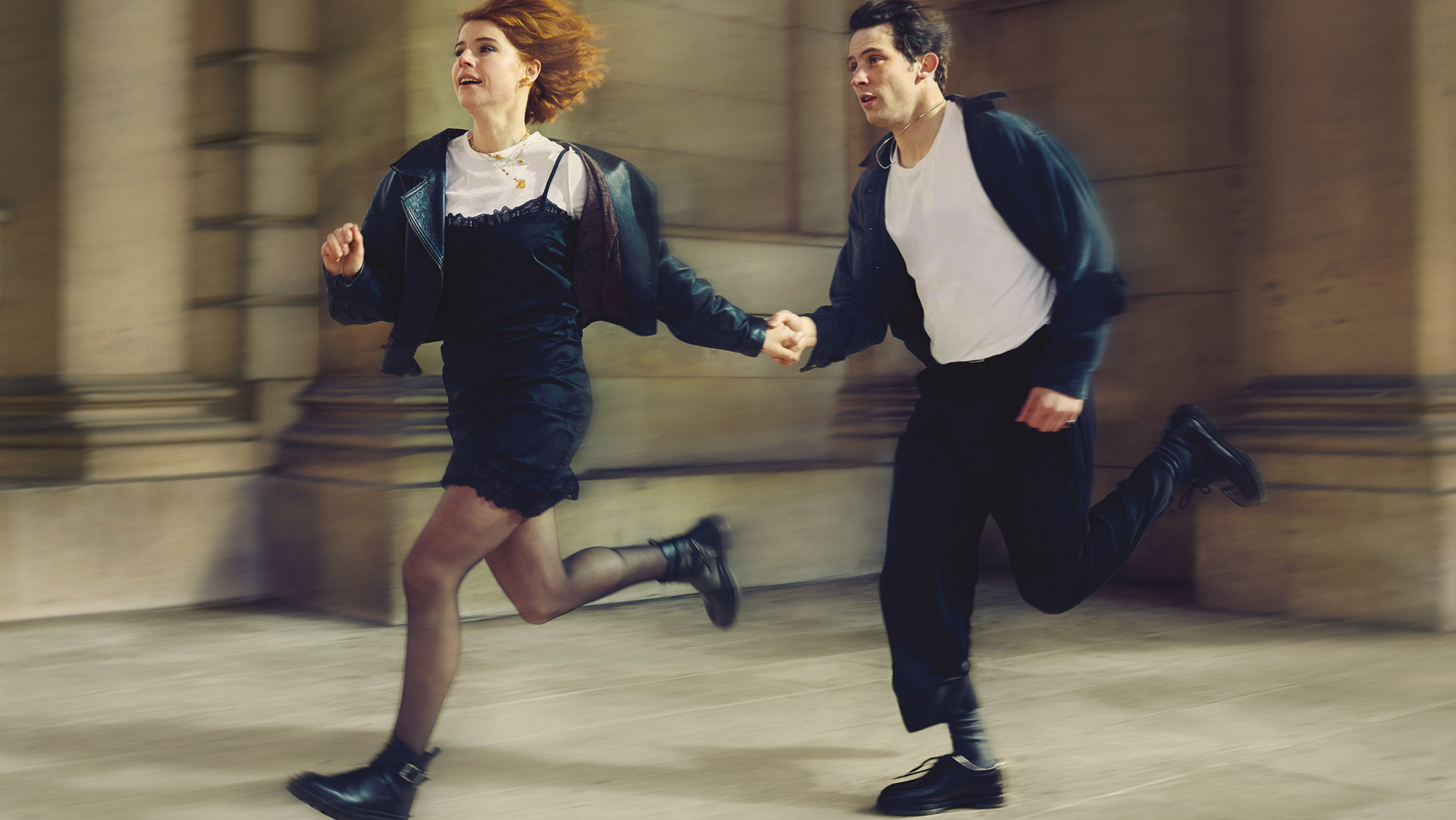 Jessie Buckley and Josh O'Connor as Juliet and Romeo in a contemporary setting, holding hands and running in front of a marble building facade.