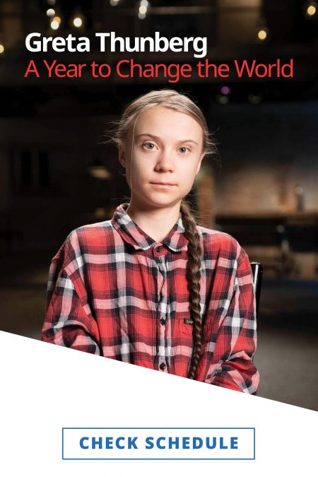 Activist Greta Thunberg with her hair in a braid over her shoulder and wearing a red plaid shirt with studio lights blurry in the background behind her.