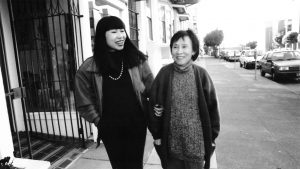 A black and white photo of Amy Tan and her mother walking down a San Francisco street in the 1990s.