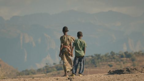 Two young Eritrean refugees holding hands and facing away from the camera