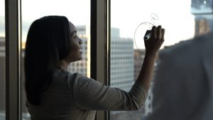 Dr Kizzmeckia Corbett drawing a diagram of a microbe on a window with a dry erase marker.