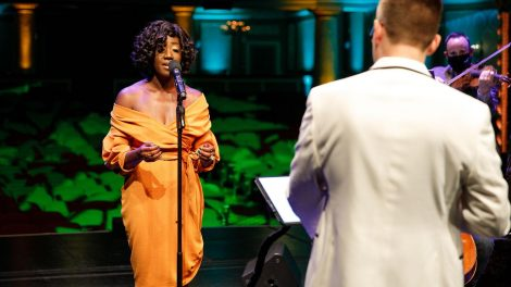 A singer in an orange wrap dress performing on stage. A conductor and a violinist are visible on the right side of the screen.