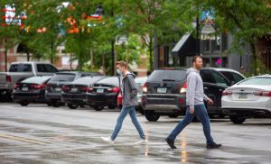 Two pedestrians - one wearing a mask, one who is not - walk the streets.