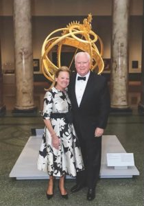 Missy Allen in a black and white dress and black heels standing with Jim Allen in a black suit and tie in front of a golden sculpture.