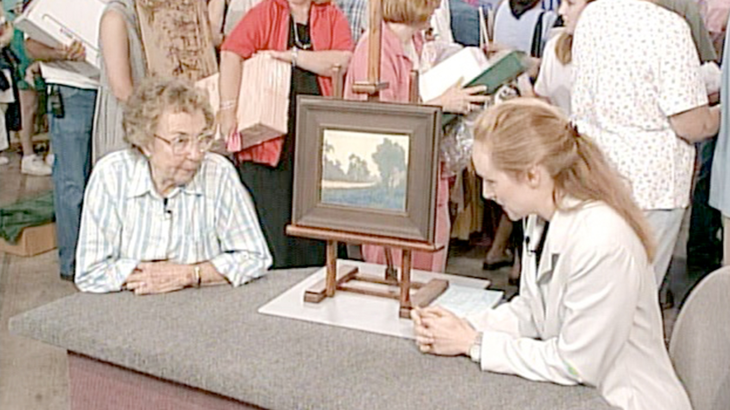 A client and an appraiser with a framed painting