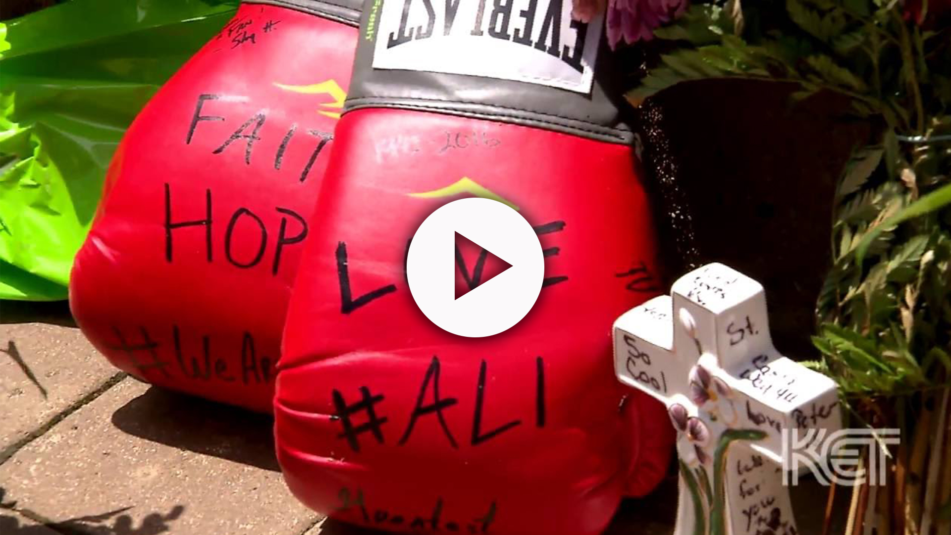 Red Everlast boxing gloves with writing on them next to a small white cross.