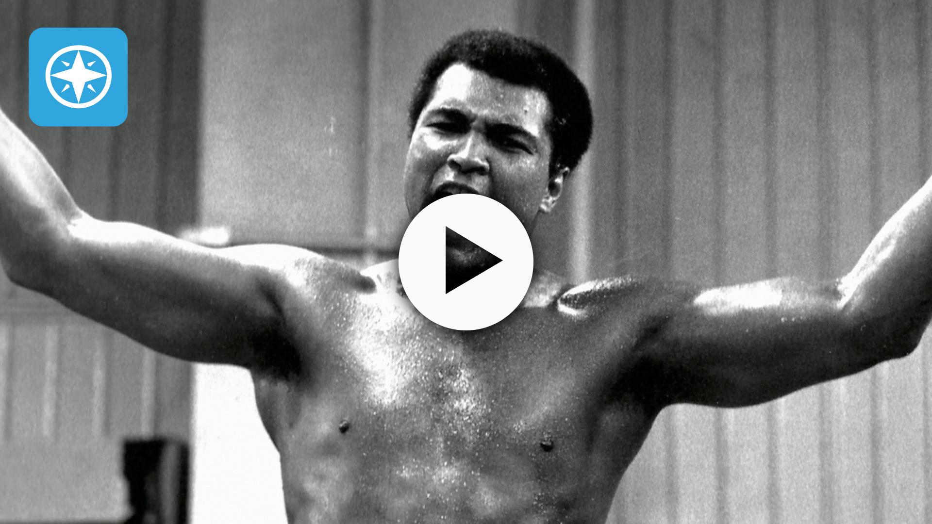 Muhammad Ali, shirtless, arms inthe air.