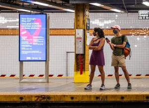 New York City commuters wear masks while they wait for the subway.