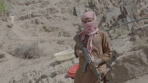 A person wearing a headscarf and holding a military rifle standing in front of a barren, rocky landscape