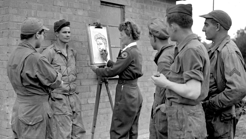 A black-and-white photo of a woman drawing a portrait of a soldier at an easel while a group of soldiers stand around her.