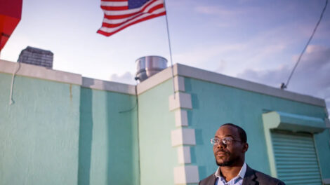 A man standing next to a teal-colored building with an American flag waving atop it