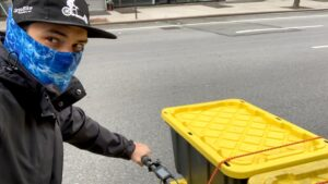 """A selfie by a bike delivery driver wearing a """"Cargo Bike"""" hat and a blue face mask."""
