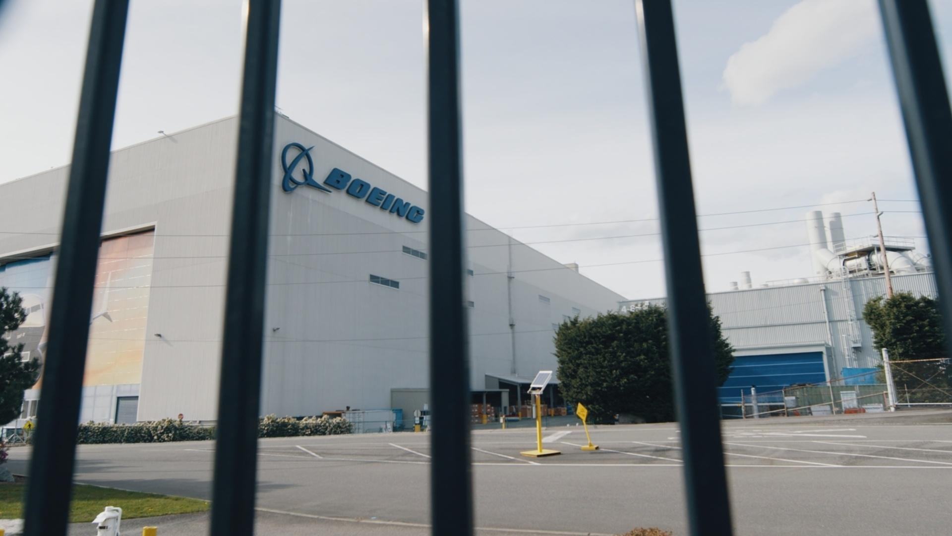 The outside of a Boeing plant seen through the bars of a gate