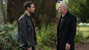 Jake (Jamie Sives) and Max (Mark Bonnar) standing near a large tree having a serious conversation.