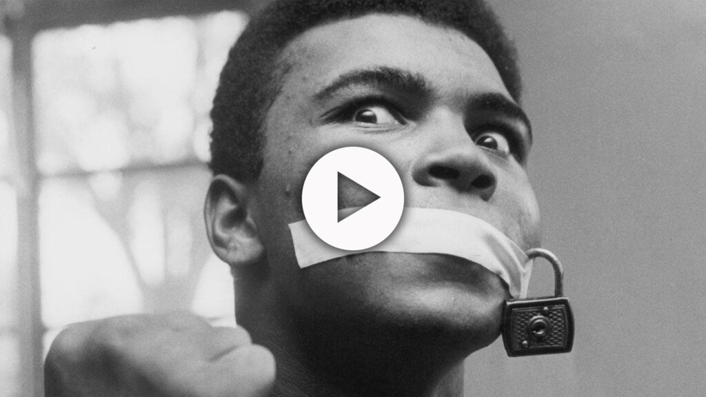 A close-up black-and-white photo of Muhammad Ali with a piece of tape across his mouth holding a padlock in place. The knuckles of his raised right fist are visible.