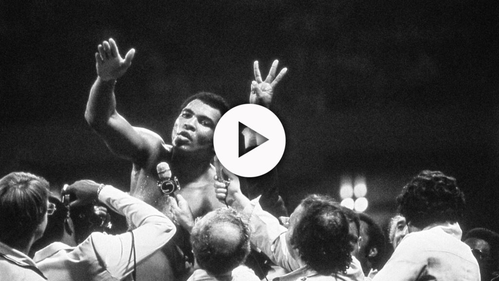 Muhammad Ali, hand in the air, talking to reporters.