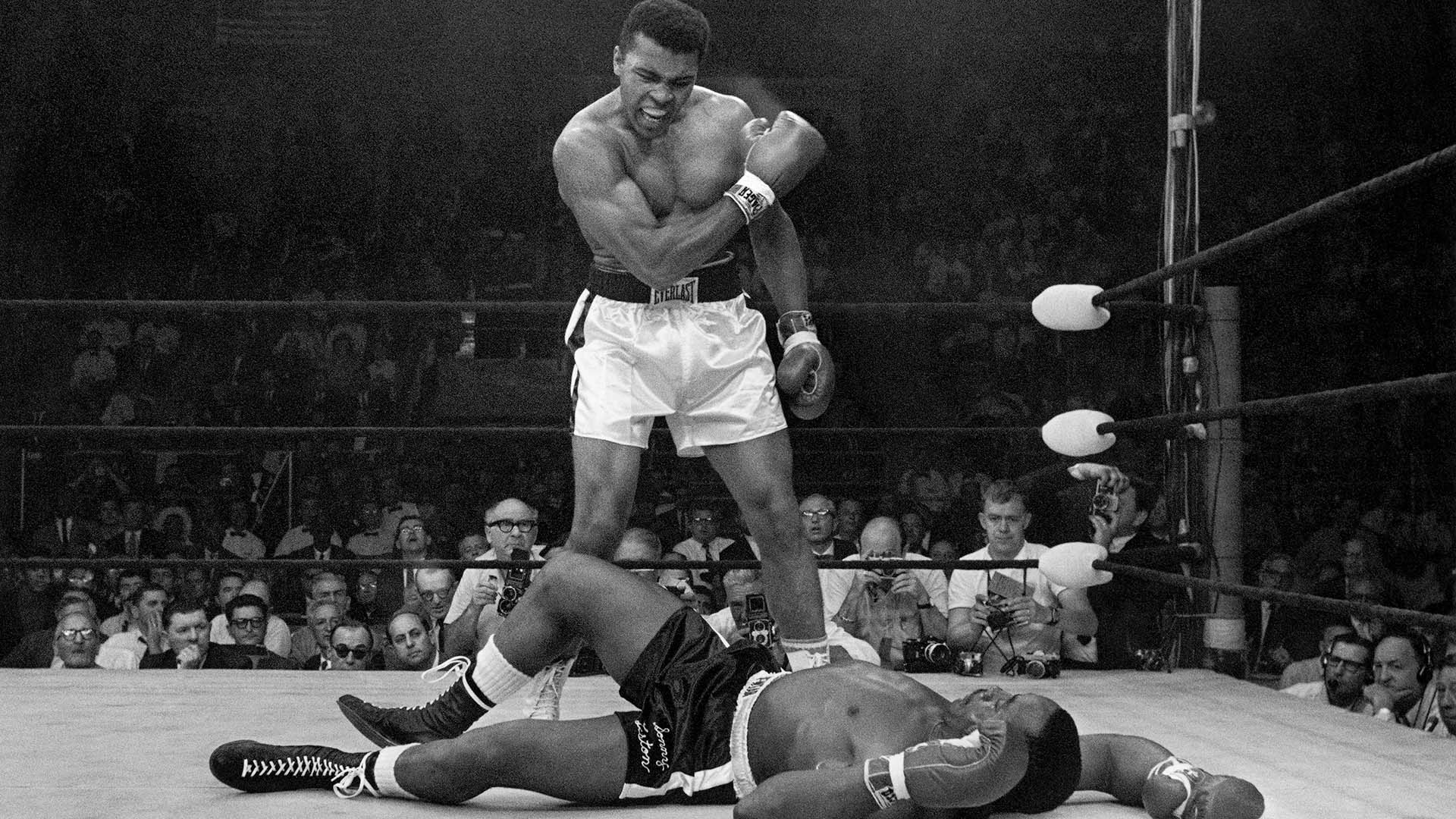 Muhammad Ali stands over fallen Sonny Liston, shouting and gesturing shortly after dropping Liston with a short hard right to the jaw in Lewiston, Maine. May 25, 1965.
