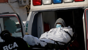 A COVID-19 patient is loaded into an ambulance.
