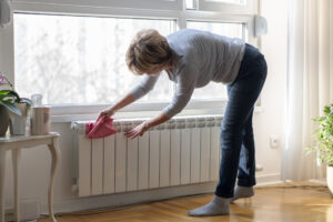 A woman cleans her living room to improve air quality.