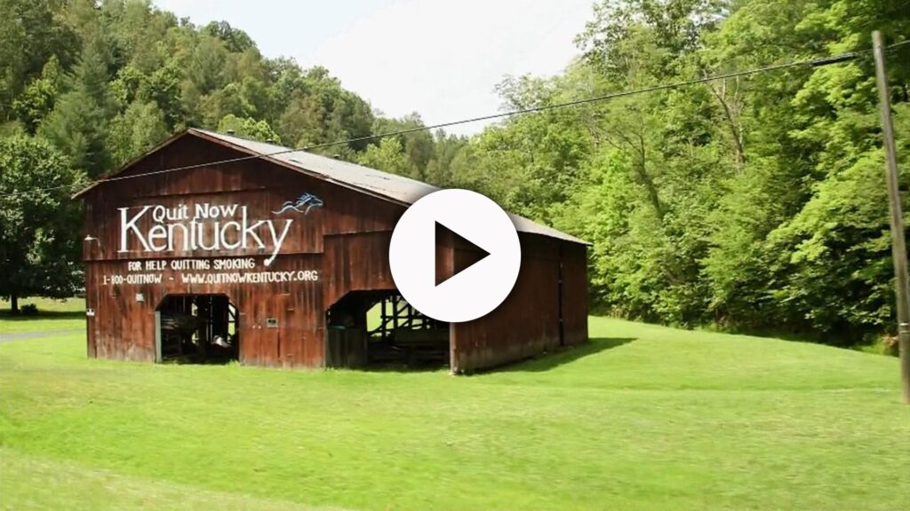 """A weathered barn sitting in a grassy field has the slogan, """"Quit Now Kentucky"""" painted in large white letters. Trees line the back of the image."""