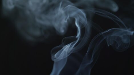 Light plumes of smoke against a black background