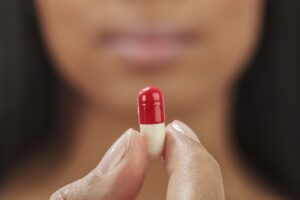 A woman holds a pill during a clinical drug trial.