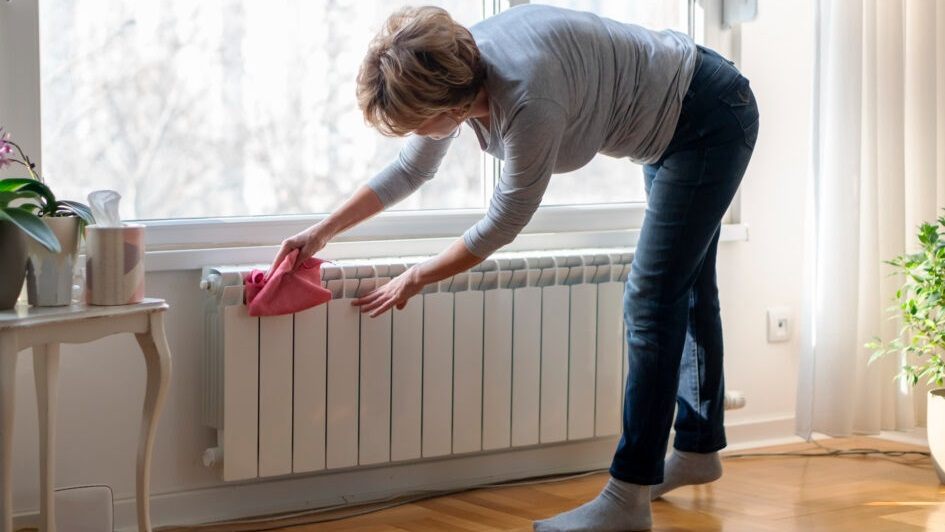 A woman leans over to wipe the top of a home radiator under a window.