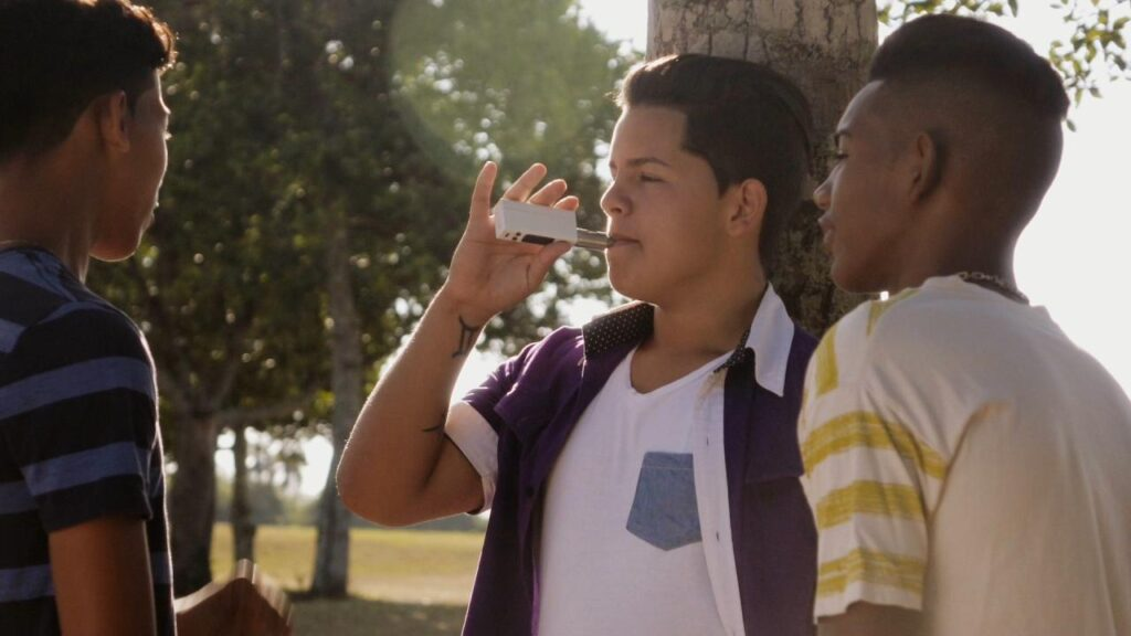 Three teen boys standing together outside. One of them is vaping. There are trees in the background.