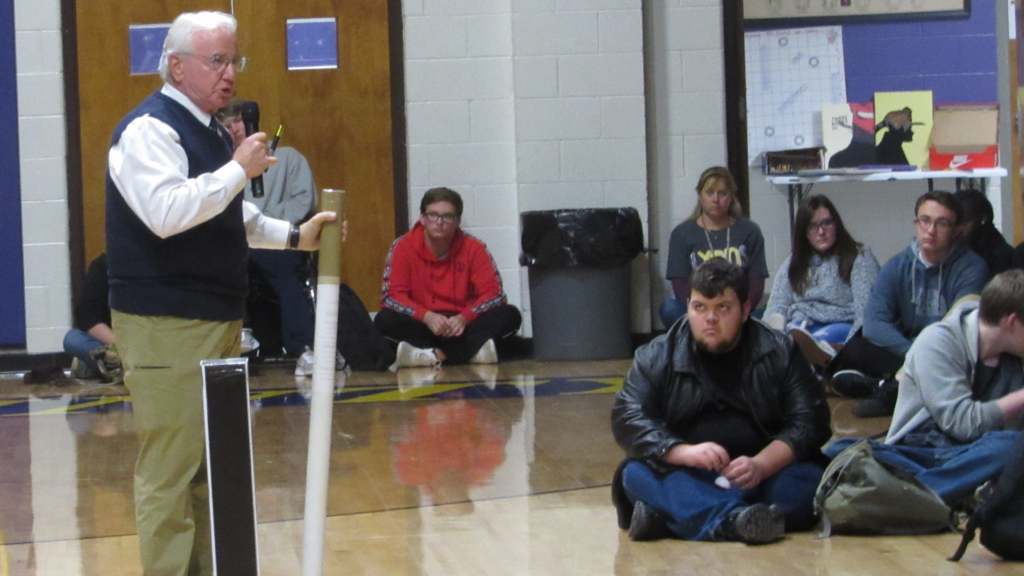 Dr. Patrick Withrow uses a giant cigarette as a prop while speaking to students.