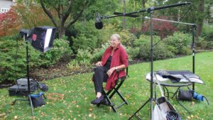 A woman sitting in a director's chair in an outdoor set surrounded by TV lights and a boom microphone