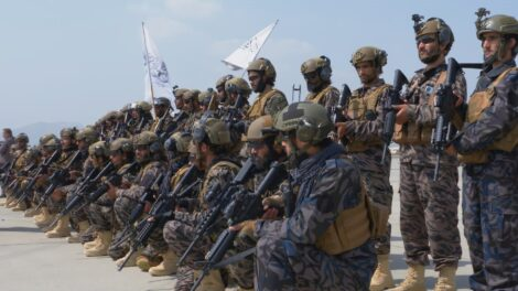 Two rows of soldiers in full combat gear, one kneeling and one standing behind them.