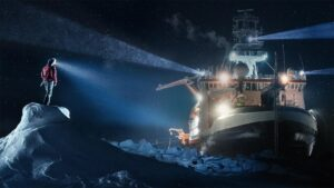 A person in cold-weather gear and a headlamp standing on top of an icy mound looking toward a ship breaking through icy water in the dark.
