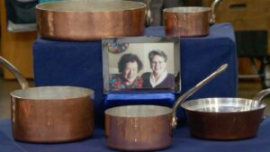 A collection of copper pans surrounding a framed photo of Julia Child posing with another woman.