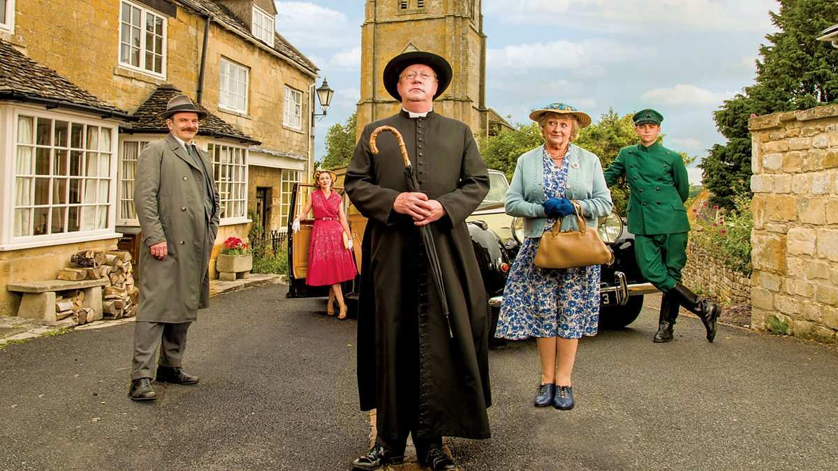 The cast of Father Brown posing on a small-town street