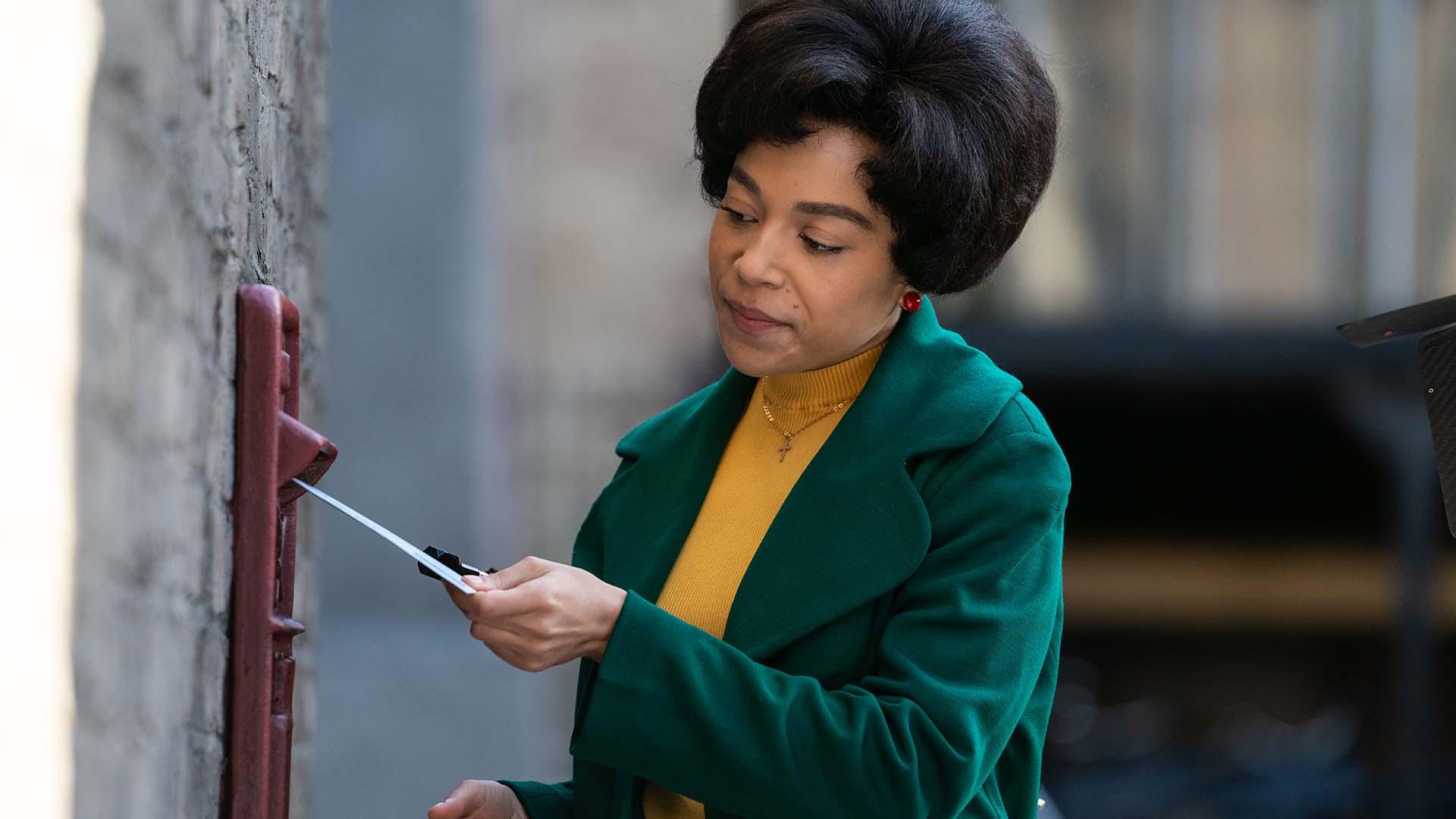 Nurse Lucille Anderson (LEONIE ELLIOTT) placing a letter into a mail slot