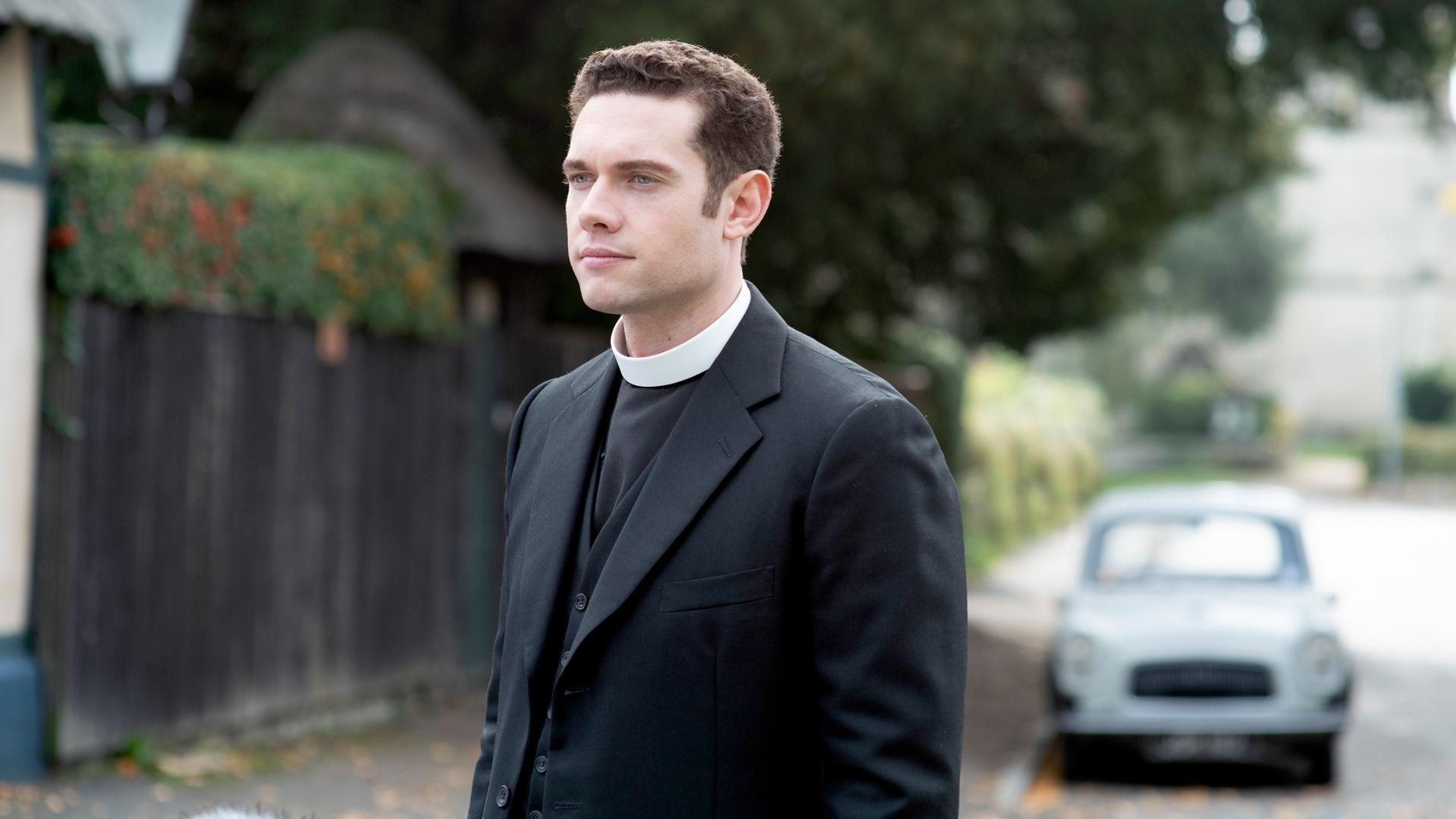 Tom Brittney as Rev. Will Davenport, standing on a quiet street